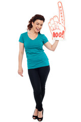 Woman cheering with large boo hurray foam hand