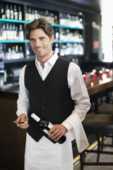 Portrait of smiling sommelier holding bottle of wine in bar