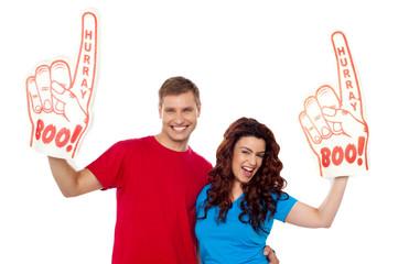 Young couple showing boo hurray foam hand