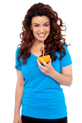 Fit girl drinking fresh orange juice directly from fruit