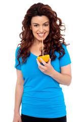 Fit girl drinking fresh orange juice directly from fruit
