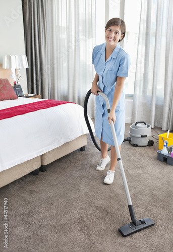 Portrait of smiling maid vacuuming hotel room