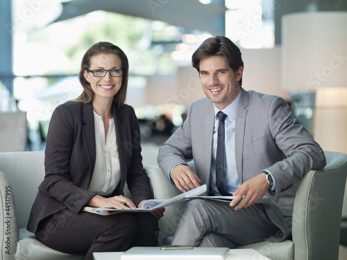 Portrait of smiling businessman and businesswoman working in lobby