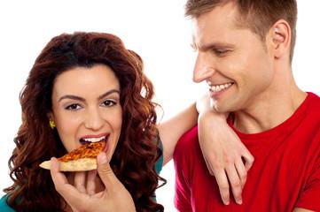 Girl enjoying pizza piece shared by her boyfriend