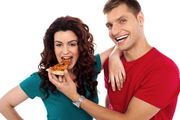 Boyfriend making her girl eat hot pizza piece