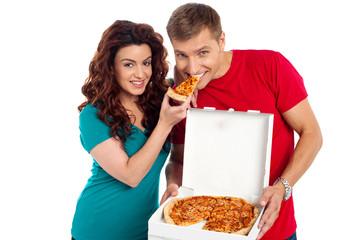 Pretty woman making her boyfriend end pizza piece