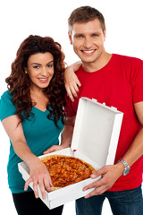 Cheerful love couple enjoying pizza together