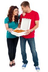 Love couple sharing pizza. Enjoying together