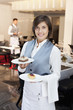 Portrait of smiling waitress holding desserts in restaurant