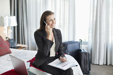 Smiling businesswoman with paperwork talking on cell phone in hotel room