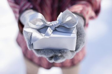 Close up of hands cupping Christmas gift with silver ribbon