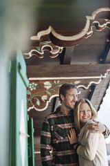Smiling couple hugging on cabin porch