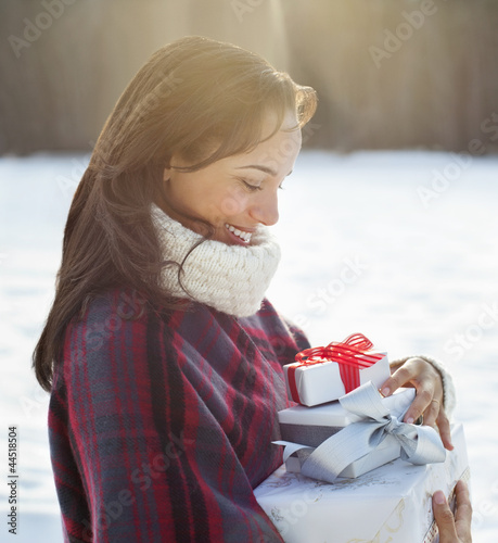 Smiling woman carrying Christmas gifts