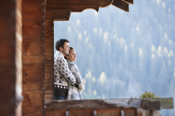 Couple hugging and looking at view from cabin porch