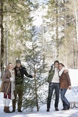 Portrait of smiling couples with fresh cut Christmas tree in woods