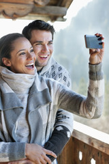 Smiling couple taking self-portrait with camera phone on cabin porch