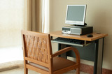 Workstation computer on table and wooden chair poster