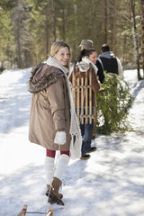 Portrait of friends with sleds and fresh cut Christmas tree in woods