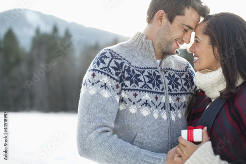 Smiling couple face to face in snowy field