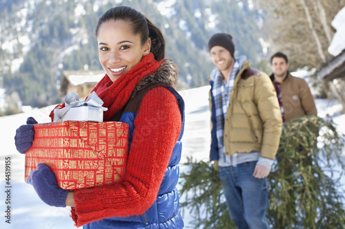 Portrait of friends with fresh cut Christmas tree and gifts in snow