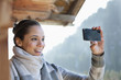 Smiling woman taking photograph with camera phone