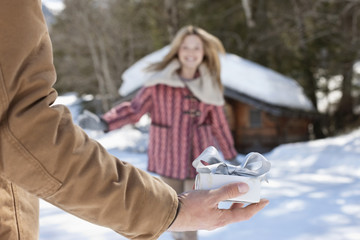 Woman running toward man holding Christmas gift in snow
