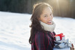 Portrait of smiling woman holding Christmas gifts in snow