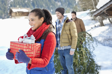 Smiling friends with fresh cut Christmas tree and gifts in snow
