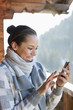 Smiling woman checking cell phone on cabin porch