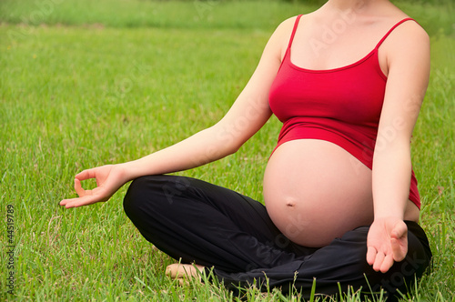 pregnant woman meditating in nature, practice yoga