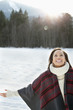 Smiling woman with head back and arms outstretched in snow