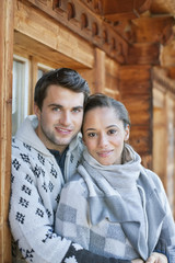 Portrait of smiling couple hugging on cabin porch