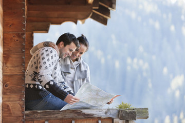 Smiling couple looking at map on cabin porch