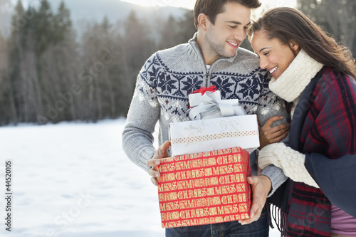 Smiling couple hugging and holding Christmas gifts in snow