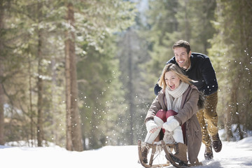 Man pushing woman on sled in snowy woods