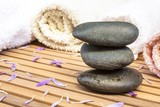 zen stones with petals and towels on slatted wood background