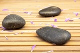 zen stones with petals on  slatted wood background