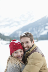 Portrait of smiling couple standing in snow
