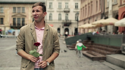 Young man with rose waiting for his date in the city