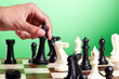 Human hand moves king on chessboard