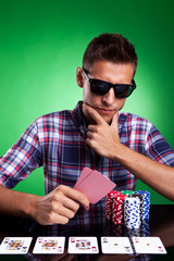 man looking thoughtfully at his poker hand