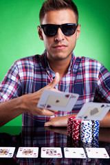Young casual poker player throwing a pair of aces