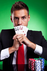 card player covering his mouth with four aces