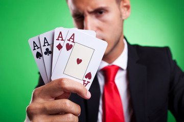 young business man showing a four of a kind hand of aces