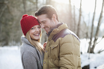 Portrait of smiling couple in snowy woods