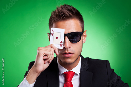 business man covers one eye with an ace of hearts
