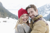 Portrait of smiling couple hugging in snow
