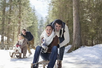 Smiling couples sledding in snowy woods