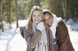Portrait of smiling friends hugging in snowy woods