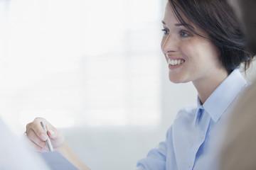Smiling businesswoman holding pen